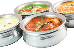 Indisk mat i metall bowlar på vit bakgrund Arkivbild