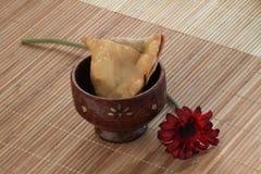 Indisk mat kryddiga Samosa med en blomma på träbakgrund Royaltyfri Fotografi