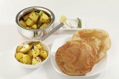 Indisk maträtt stekt potatis med spiskummin tillsammans med Puri det stekte indiska brödet Royaltyfri Bild