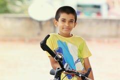Indisk pojke med cykeln Arkivfoton