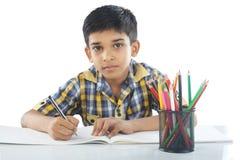 Indisk pojke med den teckningsanmärkningen och blyertspennan Arkivbilder