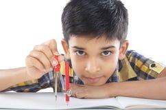 Indisk pojke med den teckningsanmärkningen och blyertspennan Royaltyfri Fotografi