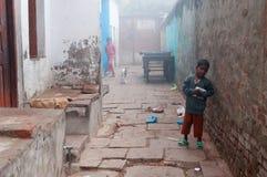 Indisk pojke på den kalla dimmiga vintermorgonen för gata i Varanasi Royaltyfri Fotografi