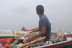 Indisk säljare som säljer souvenir på Ganges River Arkivbild