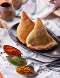 Indisk samosa med kryddor på skedarna Royaltyfri Foto