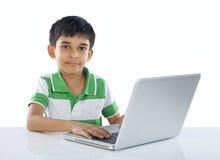 Indisk skolapojke med bärbara datorn Royaltyfri Fotografi