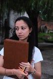 Indisk student som tänker, med en penna och en folioark i hand om framtida resultat royaltyfri bild