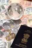 Indisk valuta med jordklotet och passet Royaltyfri Foto