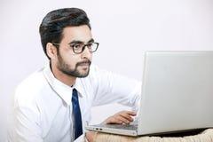 Indiska anblickar och arbete för kläder för ung man på bärbara datorn royaltyfri fotografi
