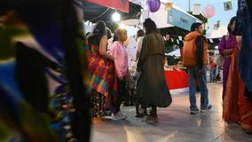 Indiska folk- och utlänninghandelsresande som går loppbesök och shoppar produkten på den thai marknaden för festivalgatanatt stock video
