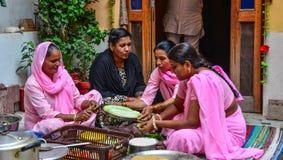 Indiska kvinnor som lagar mat traditionell mat arkivbild