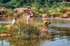 Indiska kvinnor tvättar hennes kläder i floden Royaltyfri Bild