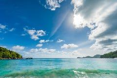 Indiska oceanenvatten och strand i Seychellerna, Mahe ö Moutain och skog i bakgrund royaltyfria foton