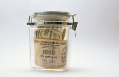 Indiska pengar eller rupie eller valuta eller sedlar i den glass kruset Royaltyfri Bild