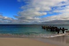Indiskt hav-, himmel- och smaragdgräsplanhav med den gamla bryggan royaltyfria bilder