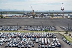 Indistrual zone with numerous cars and wharehouse as well as port cranes. stock photo