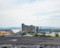 Indistrual zone with numerous cars and wharehouse as well as port cranes. stock image