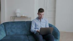 Indivíduo à moda feliz novo na camisa azul que conversa com seus amigos Sorri e datilografando no portátil usando a mensagem vídeos de arquivo