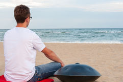 Indivíduo à moda novo que senta-se na praia da areia perto de handpan ou no cair com o mar no fundo O cair é étnico tradicional Imagens de Stock Royalty Free