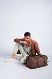 Indivíduo à moda que senta-se no assoalho com um saco do curso Fotos de Stock Royalty Free
