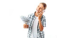 Indivíduo adolescente considerável com dinheiro em suas mãos, falando no telefone, homem alegre que guarda dólares, no estúdio no foto de stock