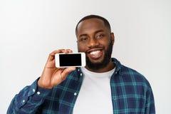 Indivíduo africano considerável isolado no fundo cinzento, apresentando o telefone esperto e apontando com o dedo na tela preta v fotos de stock royalty free