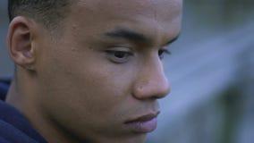 Indivíduo afro-americano comprimido que pensa sobre sua vida, assento só exterior filme
