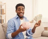 Indivíduo afro-americano entusiasmado que guarda o piggybank e as notas de dólar fotos de stock royalty free