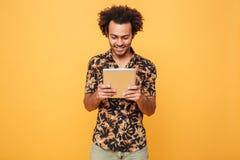Indivíduo afro-americano novo de sorriso que está e que usa a tabuleta do PC foto de stock