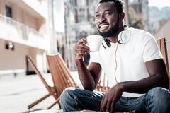 Indivíduo afro-americano pensativo que sorri ao pensar sobre algo agradável imagens de stock