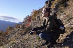 Indivíduo agradável novo com a trouxa nas montanhas que olham na distância e que guardam uma câmera fotografia de stock