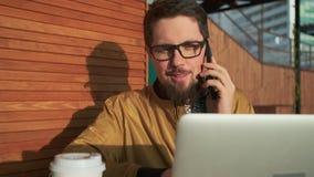 Indivíduo agradável que fala no telefone ao usar o PC fora filme