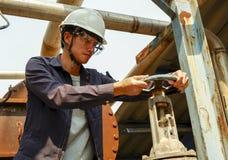 Indivíduo asiático que veste um capacete que gerencie a válvula da tubulação de água no processo de produção foto de stock