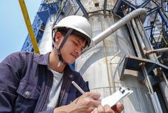 Indivíduo asiático que veste um funcionamento do capacete em uma grande fábrica industrial que verifica o processo de produção fotos de stock