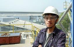 Indivíduo asiático que veste um funcionamento do capacete em uma grande fábrica industrial que verifica o processo de produção foto de stock royalty free