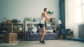 Indivíduo ativo que salta em casa fazendo esportes no assoalho de praticar liso que dá certo filme