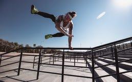 Indivíduo atlético vestido no t-shirt branco, nas caneleiras pretas e no short azul fazendo o truque que salta sobre os trilhos s foto de stock