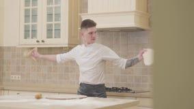 Indivíduo atrativo que gerencie e que lanç dois discos da massa da pizza na cozinha em casa Pizzaiolo profissional que faz a pizz video estoque