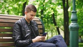 Indivíduo atrativo que usa um smartphone ao sentar-se em um banco no parque video estoque