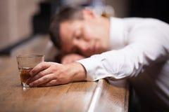 Indivíduo bêbado e inconsciente que encontra-se no contador Foto de Stock Royalty Free
