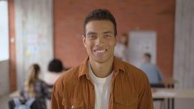 Indivíduo bem sucedido feliz do estudante close-up do retrato um homem de raça misturada no fundo da audiência durante uma leitur video estoque