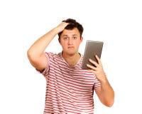 Indivíduo chocado que olha a câmera e que guarda um tablet pc indivíduo emocional no fundo branco fotos de stock