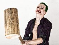 Indivíduo com a cara louca do palhaço, cabelo verde e sorriso idiota traje carnaval guardando o martelo para o grilo foto de stock royalty free