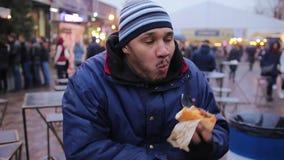 Indivíduo com fome desabrigado que come o cachorro quente charity Comida lixo, colesterol, obesidade video estoque