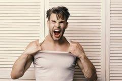 Indivíduo com músculos fortes e cerda na camiseta de alças branca Homem com cabelo justo no fundo de madeira claro das pranchas foto de stock