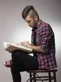 Indivíduo com o mohawk que lê um livro Imagem de Stock Royalty Free