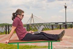 Indivíduo com o portátil no parque Imagens de Stock