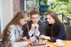 Indivíduo considerável e namoradas espertas que jogam a xadrez em um fundo do café Conceito dos jogos da inteligência Fotografia de Stock Royalty Free