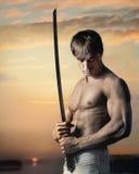 Indivíduo considerável muscular com a espada no por do sol fotos de stock