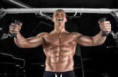 Indivíduo considerável novo que faz exercícios no gym fotos de stock